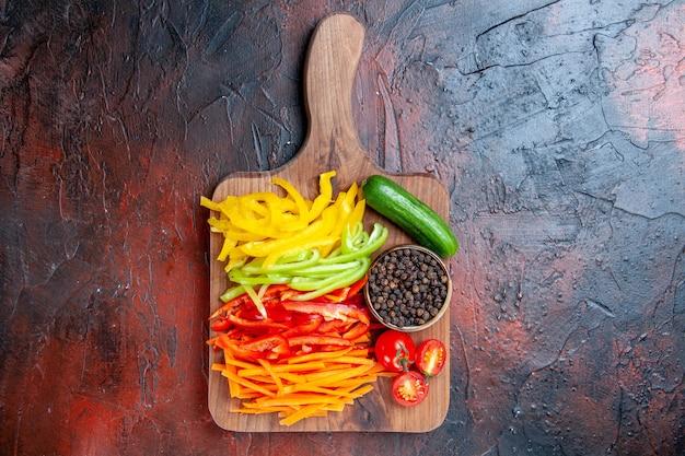 Vista dall'alto colorato peperoni tagliati pepe nero pomodori cetriolo sul tagliere sullo spazio libero tavolo rosso scuro