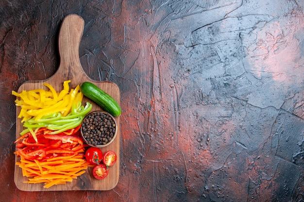 Vista dall'alto colorato peperoni tagliati pepe nero pomodori cetriolo sul tagliere sul tavolo rosso scuro con spazio di copia