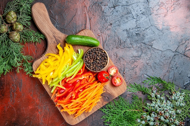 Top view colorful cut peppers black pepper tomatoes cucumber on cutting board pine branches on dark red table free space