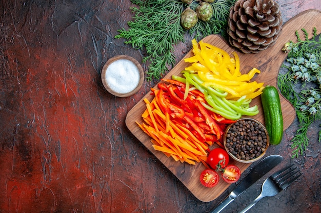 Vista dall'alto peperoni colorati pepe nero pomodori cetriolo sul tagliere sale forchetta e coltello sul tavolo rosso scuro con spazio libero