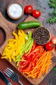 Vista dall'alto peperoni colorati pepe nero pomodori cetriolo sul tagliere sale forchetta e coltello sul tavolo rosso scuro