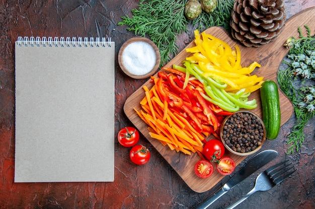 Vista dall'alto peperoni colorati pepe nero pomodori cetriolo sul tagliere sale forchetta e blocco note coltello sul tavolo rosso scuro