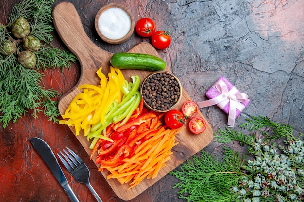 Top view colorful cut peppers black pepper tomatoes cucumber on cutting board salt fork and knife small gift on dark red table