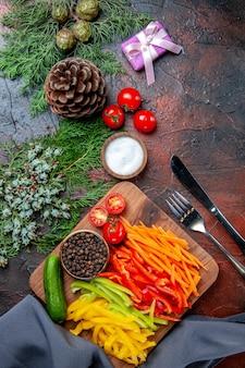 Vista dall'alto peperoni colorati pepe nero pomodori cetriolo sul tagliere piccolo regalo rami di pino sale coltello e forchetta sul tavolo rosso scuro