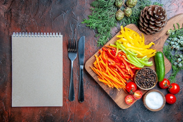 Вид сверху красочный нарезанный перец черный перец помидоры огурец на разделочной доске ноутбук соль, нож и вилка на темно-красном столе