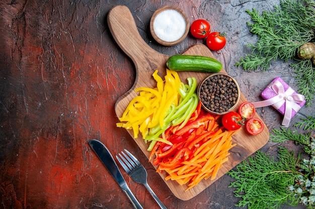 Вид сверху красочный нарезанный перец черный перец помидоры огурец на разделочной доске соль, вилка и нож небольшой подарок на темно-красном столе