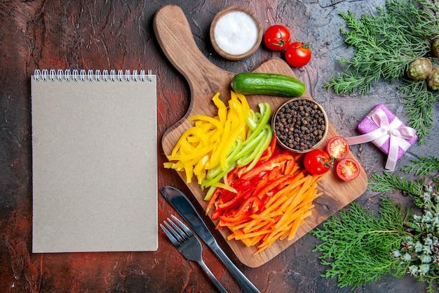 Вид сверху красочный нарезанный перец черный перец помидоры огурец на разделочной доске соль вилка нож ноутбук на темно-красном столе