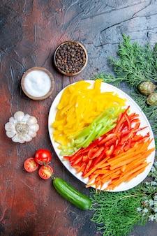 어두운 빨간색 테이블 여유 공간에 접시 소금과 후추 토마토 마늘 오이에 상위 뷰 다채로운 잘라 고추