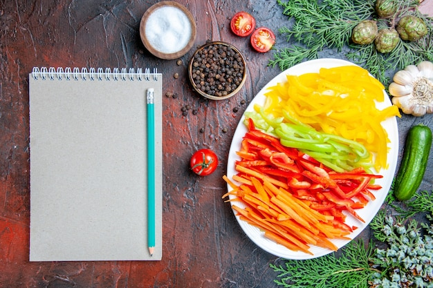 平面図カラフルなカットペッパープレートソルトとブラックペッパートマトガーリックキュウリ鉛筆メモ帳ダークレッドテーブル