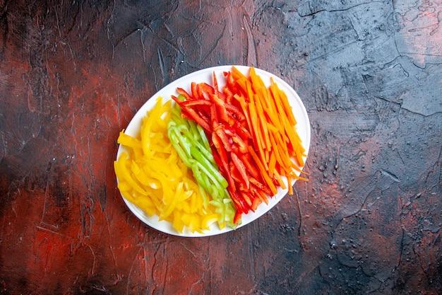 어두운 빨간색 테이블 여유 공간에 흰색 접시에 상위 뷰 다채로운 잘라 고추