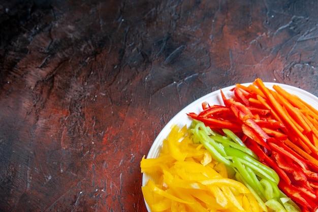 Вид сверху красочного нарезанного перца на белой тарелке на темно-красном столе с копией пространства
