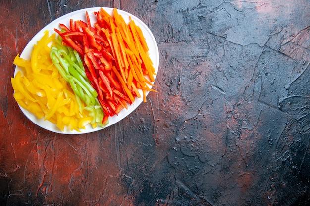 Вид сверху разноцветного нарезанного перца на белой тарелке на темно-красном столе со свободным местом