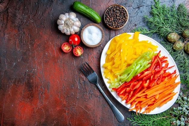 Vista dall'alto peperoni colorati tagliati su piastra forcella sale e pepe nero pomodori aglio cetriolo su spazio libero tavolo rosso scuro
