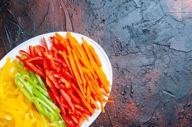 Top view colorful cut peppers on white plate on dark red table copy space