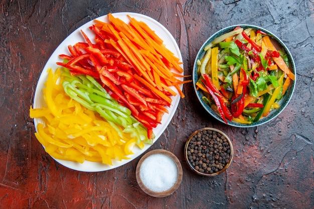 Vista dall'alto peperoni colorati tagliati su insalata di verdure piatto bianco nella ciotola pepe nero sale aglio sul tavolo rosso scuro