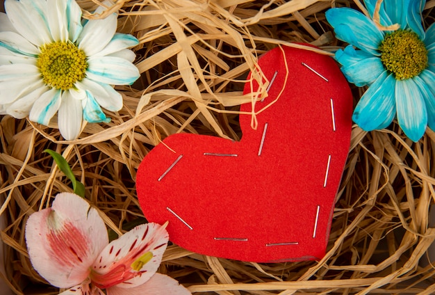 Top view of colorful daisy flowers and pink alstroemeria with a heart made from red color paper on straw table