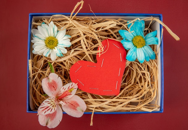 Top view of colorful daisy flowers and pink alstroemeria with a heart made from red color paper and with straw in a blue present box on red table