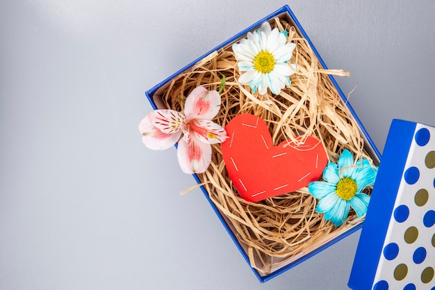 Top view of colorful daisy flowers and pink alstroemeria with a heart made from red color paper and with straw in a blue present box on white table with copy space