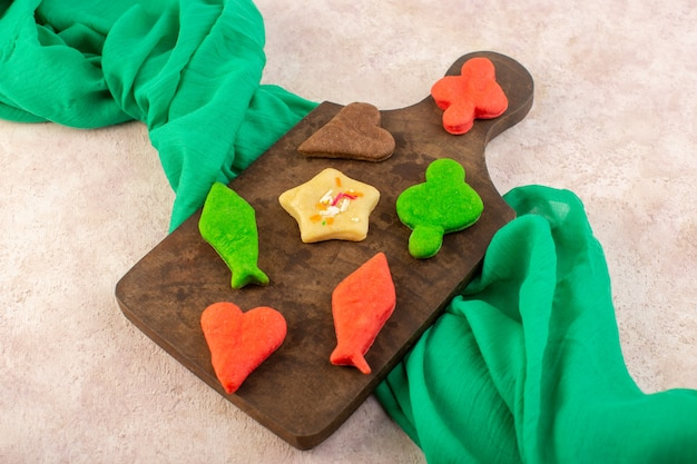 Top view of colorful delicious cookies different formed on the brown wooden desk