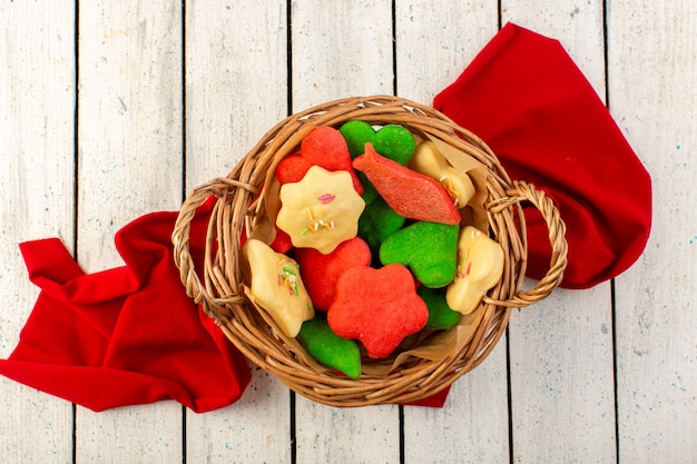A top view colorful delicious cookies different formed inside brown basket on the grey surface