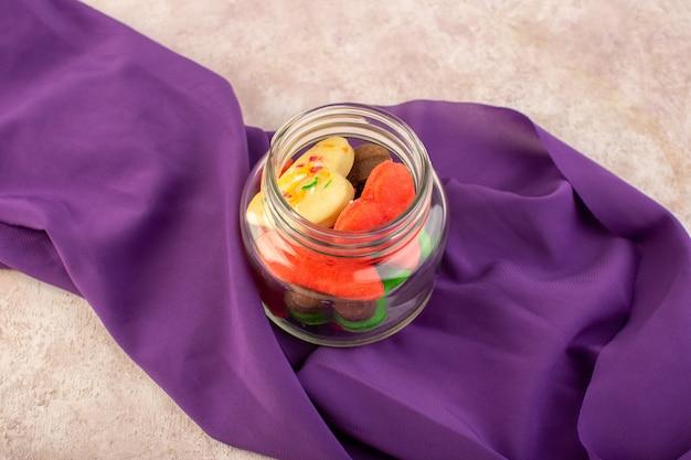 Vista dall'alto di diversi deliziosi biscotti colorati formati all'interno possono sul tessuto viola e superficie rosa