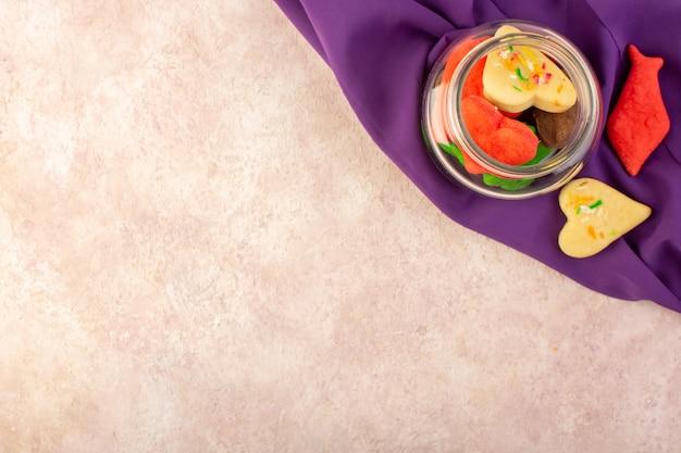 Vista dall'alto di diversi deliziosi biscotti colorati formati all'interno possono sul tessuto viola