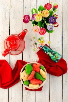 Vista dall'alto di diversi deliziosi biscotti colorati formati all'interno piatto con bollitore rosso caramelle e fiori