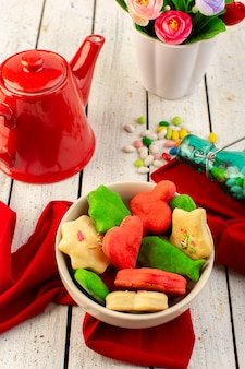 Top view of colorful delicious cookies different formed inside plate with red kettle candies and flowers