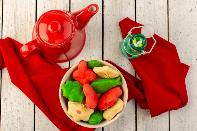 Top view of colorful delicious cookies different formed inside plate with red kettle and candies