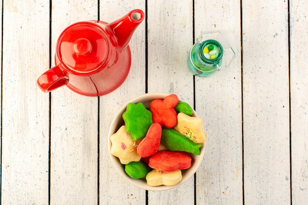 Top view of colorful delicious cookies different formed inside plate with red kettle on the grey surface