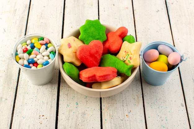 Top view of colorful delicious cookies different formed multicolored inside plate with candies