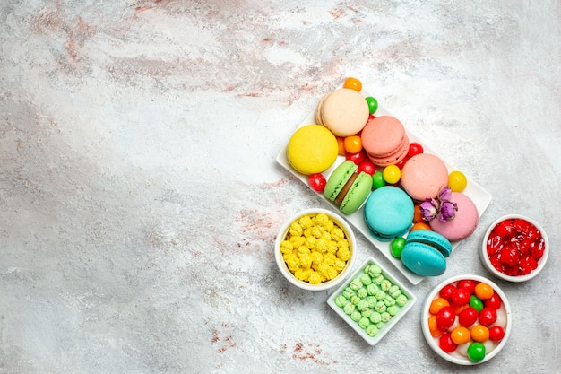 Top view colorful delicious macarons little cakes with candies on light white space