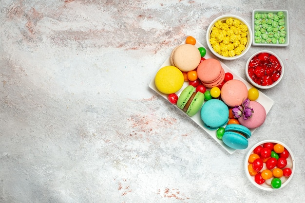 Вид сверху красочные вкусные макароны маленькие пирожные с конфетами на светлом белом пространстве