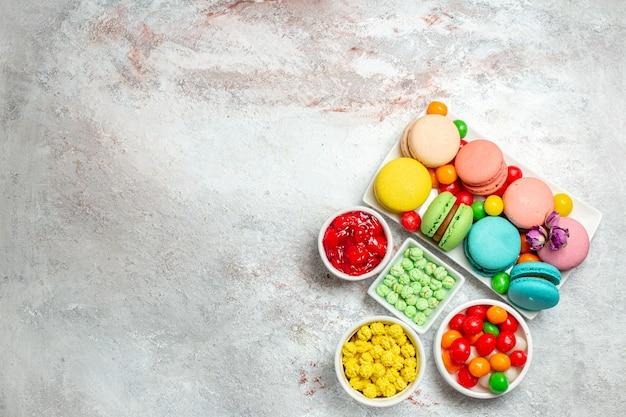 Vista dall'alto colorati deliziosi macarons piccole torte con caramelle sulla scrivania bianca