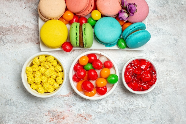 Top view colorful delicious macarons little cakes with candies on a white space