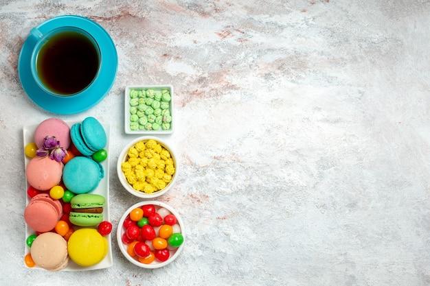Vista dall'alto colorati deliziosi macarons piccole torte con caramelle su uno spazio bianco