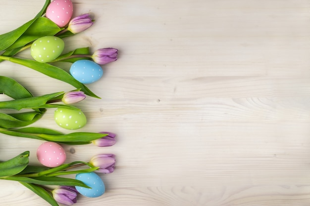 Top view of a colorful easter eggs in basket and  purple tulips on a light wood background with message space.