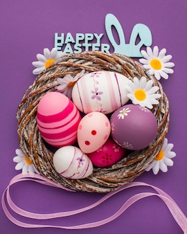 Top view of colorful easter eggs in basket with chamomile flowers