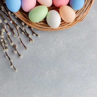 Top view of colorful easter eggs in basket with flowers and copy space