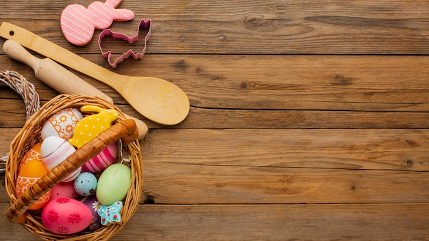 Top view of colorful easter eggs in basket with kitchen utensils and copy space