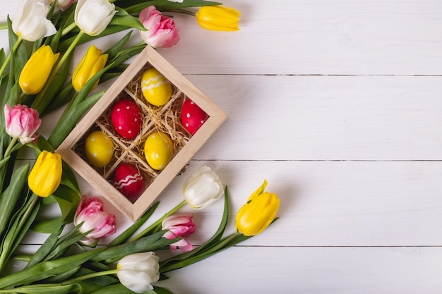 Top view of colorful easter eggs on a bed of straw in a long wooden box on a white wooden table and tulips, place for text