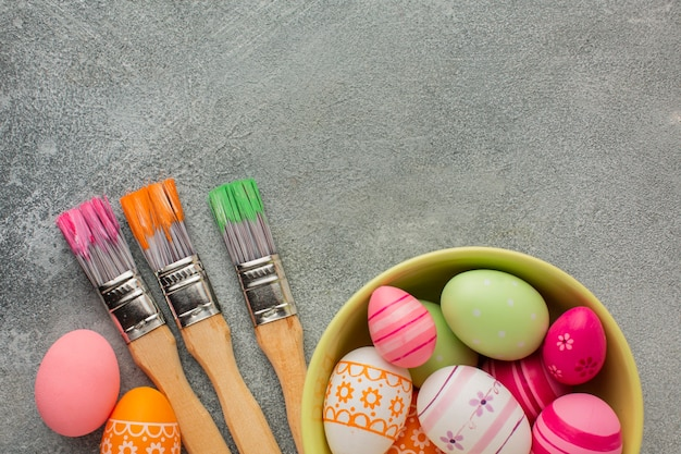 Top view of colorful easter eggs in bowl with paint brushes and copy space