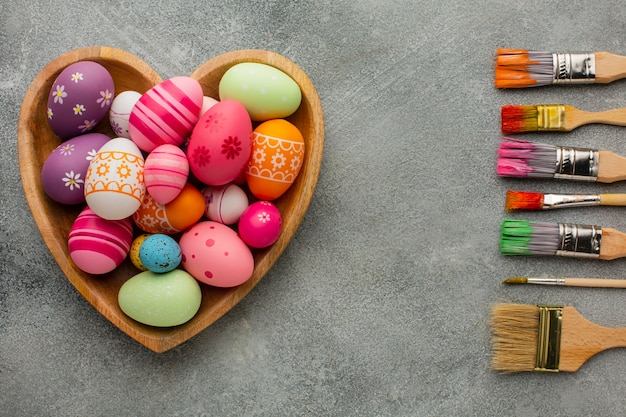 Top view of colorful easter eggs in heart shaped plate with assortment of paint brushes