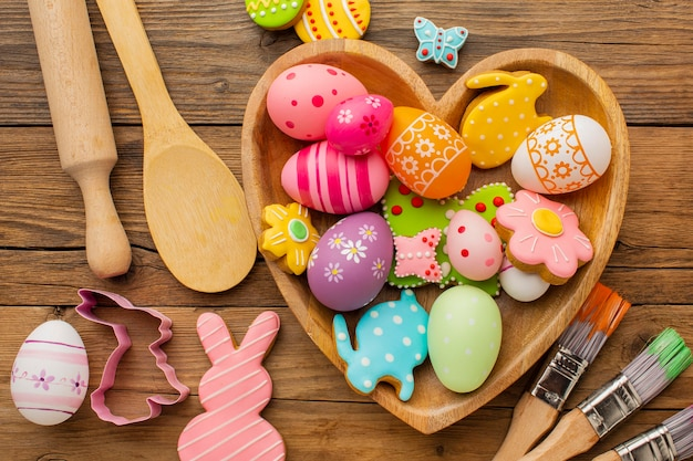 Top view of colorful easter eggs in heart shaped plate with kitchen utensils and paint brushes