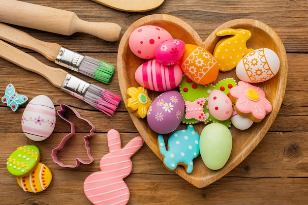 Top view of colorful easter eggs in heart shaped plate with kitchen utensils