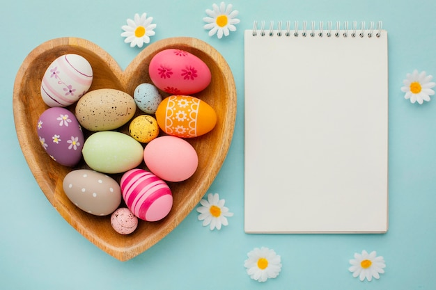 Top view of colorful easter eggs in heart-shaped plate with notebook and flowers