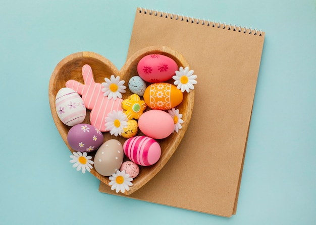 Top view of colorful easter eggs in heart-shaped plate with notebook