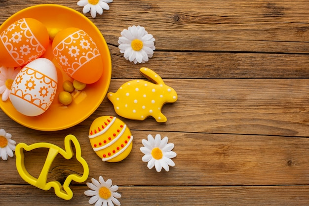 Top view of colorful easter eggs on plate with chamomile flowers and copy space