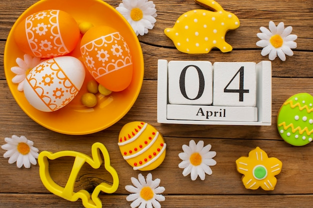 Top view of colorful easter eggs on plate with chamomile flowers and date