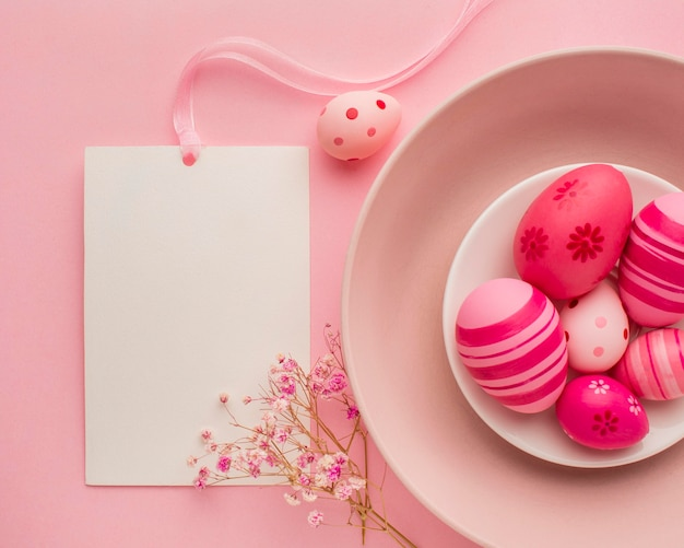 Top view of colorful easter eggs on plate with flowers and paper